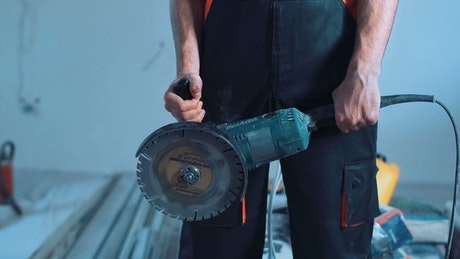 Construction worker shows a cutting tool