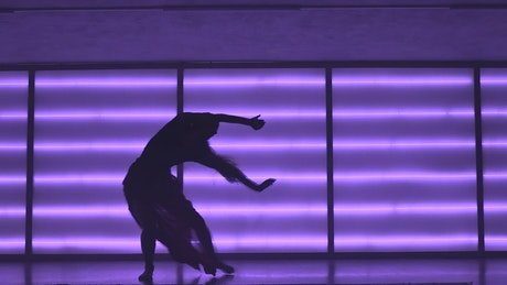 Contemporary dancer in neon-lit studio