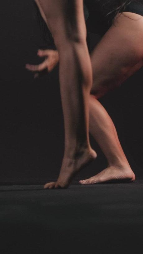 Contemporary dancers in a dark spot, knee level shot