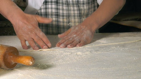 Cook preparing dough for a dish