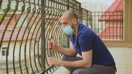 Coronavirus worries man in face mask sitting on balcony