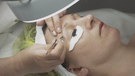 Cosmetologist cleaning an eyebrow