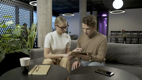 Couple brainstorming with a tablet