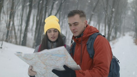 Couple checking map on hike in snowfall
