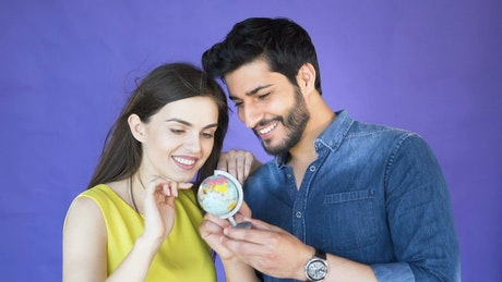 Couple choosing a place to travel with a globe