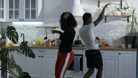 Couple dancing happily in the kitchen