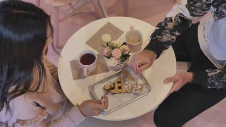 Couple eating a slice of cake with coffee on a date