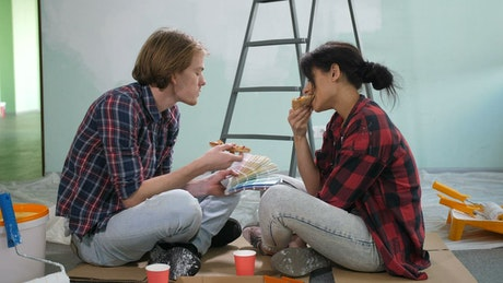 Couple eating pizza while painting