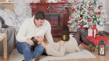 Couple enjoy Christmas romance in front of fireplace