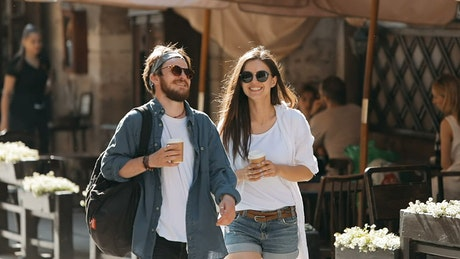 Couple enjoy friendship while walking on city street