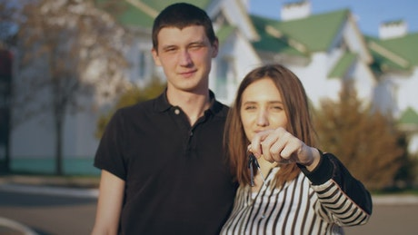 Couple happily showing keys to their new house