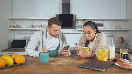 Couple having breakfast cereal and see their cell phones