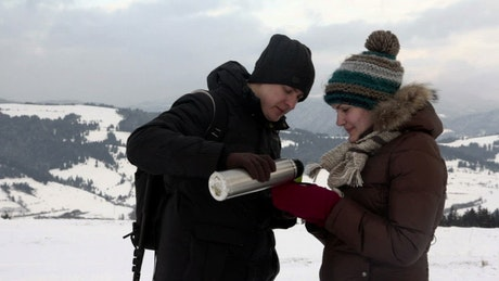 Couple having tea in a snowy mountain landscape