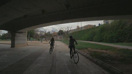 Couple heading below a bridge on bikes