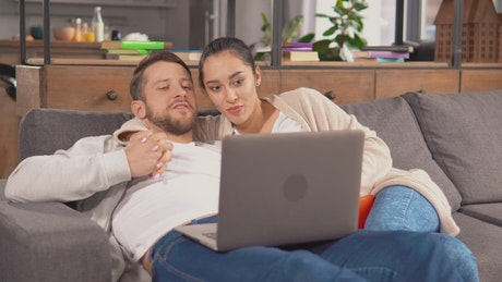 Couple holding each other in an armchair watching a movie