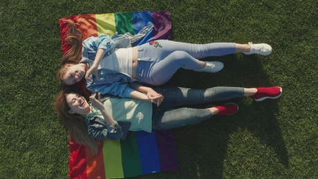 Couple laying on a rainbow flag