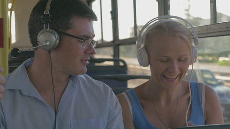 Couple listening to music on a bus