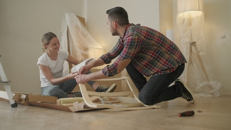 Couple look at instructions while assembling furniture