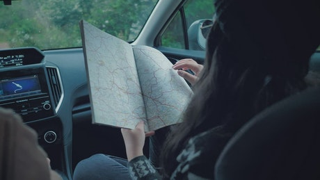 Couple of adventurers reading a map inside a car