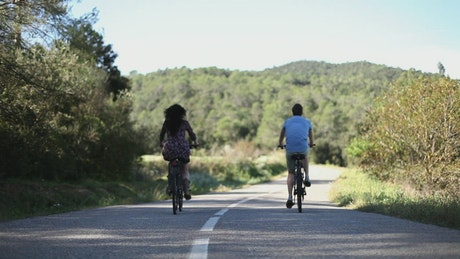 Couple of cyclists on a road in the countryside