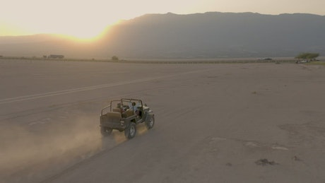 Couple of friends touring a desert by Jeep in an aerial shot
