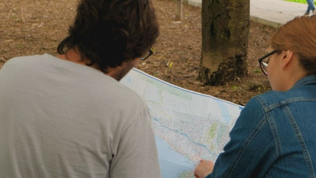 Couple of people reviewing a large map sitting in a park