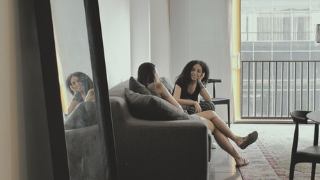 Couple of women chatting sitting inside an apartment