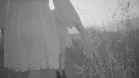 Couple of women dressed in white walking across the field