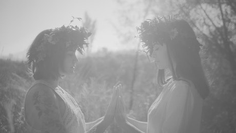Couple of women performing a small ritual with their hands together