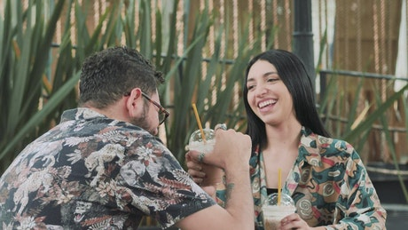 Couple on a date with coffee laughing happy