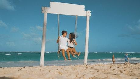 Couple on a swing on a beach