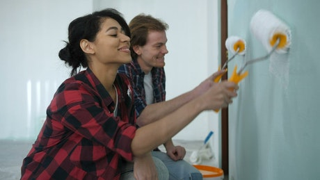 Couple painting a room at home