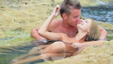Couple passionately kissing on the rocky shore of the sea