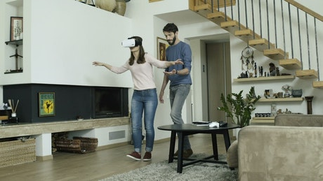 Couple playing with a virtual reality at home