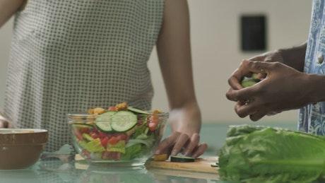 Couple preparing salad in kitchen