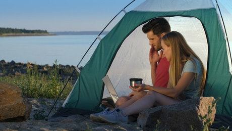 Couple relaxing while camping at the lake