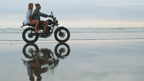 Couple riding a motorcycle in the beach