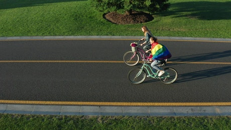 Couple riding bikes down an empty road