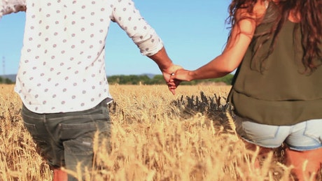 Couple running through a wheat field