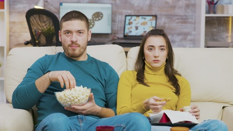 Couple shows fear while watching movie on sofa