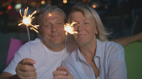 Couple smiling with sparklers