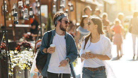 Couple stroll down sunny street with coffee