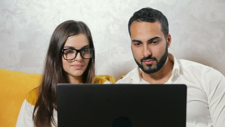 Couple surprised by what they see on their laptop