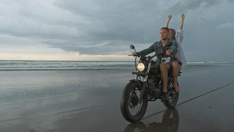 Couple touring a beach riding a motorcycle