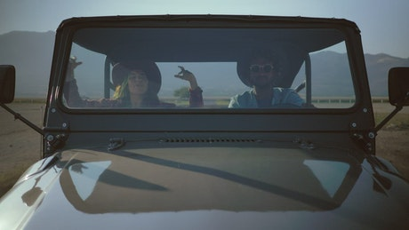 Couple traveling down a road in a Jeep
