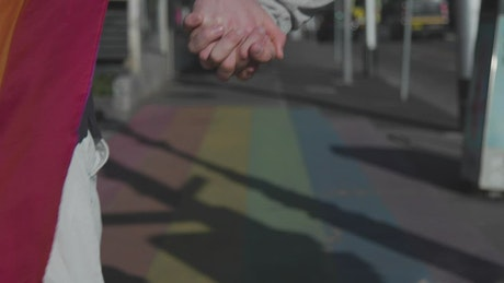 Couple walking in the street with a rainbow flag
