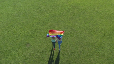 Couple walking with a rainbow flag