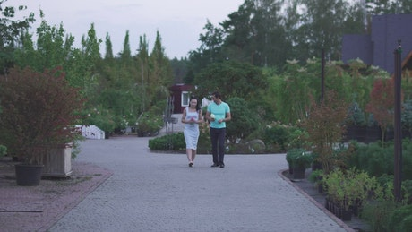 Couple walks in a garden while chatting
