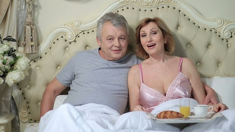Couple watching a film in bed