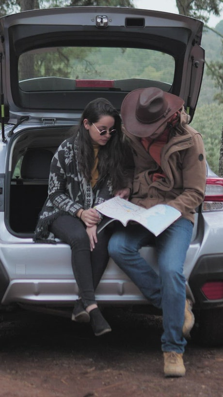 Couple watching a map in the trunk of a car